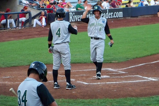 Cheslor Cuthbert (No. 8) smiles as he scores and prepares to high-five teammate Brian Fletcher (No. 4), who scored ahead of him during a 2011 Kane County Cougars game. (Photo by Craig Wieczorkiewicz/The Midwest League Traveler)