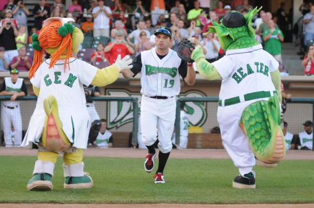 Rehabbing Joey Votto is greeted by Dragons mascots Gem and Heater as he takes the field in Dayton last year.
