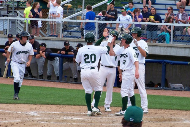 Beloit's Chris Bostick is greeted by teammates at home after hitting a 9th-inning grand slam.