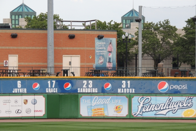 The retired jersey numbers of Wally Joyner, Mark Grace, Ryne Sandberg and Greg Maddux on the outfield wall of Peoria's Dozer Park. (Photo by Craig Wieczorkiewicz/The Midwest League Traveler)