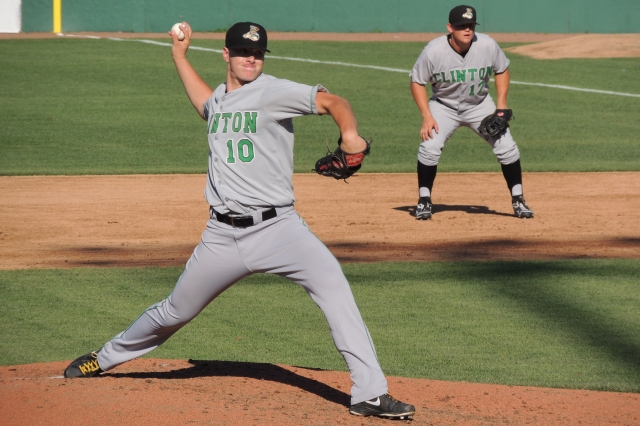 Clinton LumberKings SP Lars Huijer throws a pitch as Justin Seager plays first base behind him.