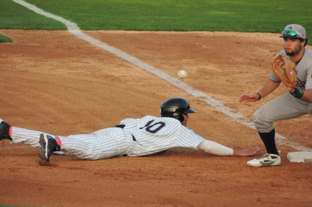 Angel Ortega slides back to first base as the baseball heads for Michael Soto's glove.