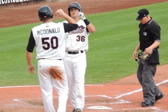 J.D. Davis is greeted at home plate by teammate Chase McDonald after hitting a two-run homer that gave the River Bandits a 4-2 lead.