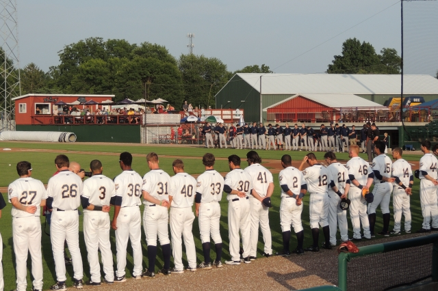 The Burlington Bees (foreground) and the Cedar Rapids Kernels lined up in front of their dugouts for the moment of silence honoring Susan Denk.
