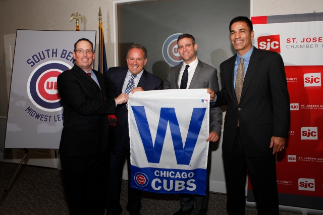 From left: Joe Hart, Andrew Berlin, Theo Epstein and Jason McLeod hold a Cubs win flag at the end of Thursday's press conference. (Photo provided by the South Bend Cubs)