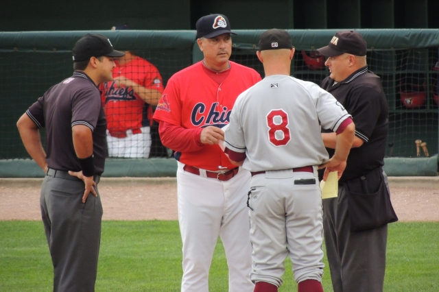 Peoria Chiefs manager Joe Kruzel and Wisconsin Timber Rattlers manager Matt Erickson meet with umpires before a game in Peoria. (Photo by Craig Wieczorkiewicz/The Midwest League Traveler)
