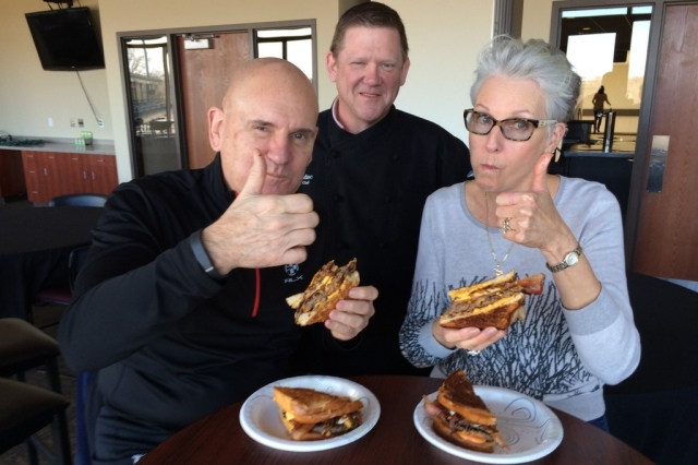 "Kane County Cougars owners Dr. Bob and Cheryl Froehlich sample the new ""Heart Attack Burger"" available at Fifth Third Bank Ballpark this year. (Photo courtesy of the Kane County Cougars)"