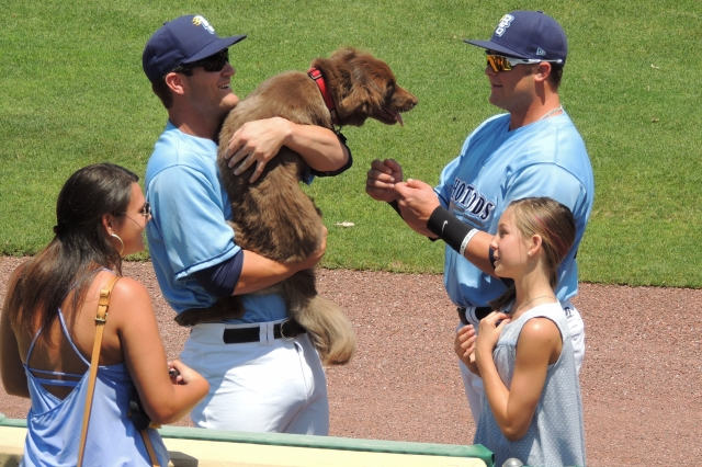 Hunter Lockwood (right) reaches out to pet a dog held by teammate Nick Ciuffo.