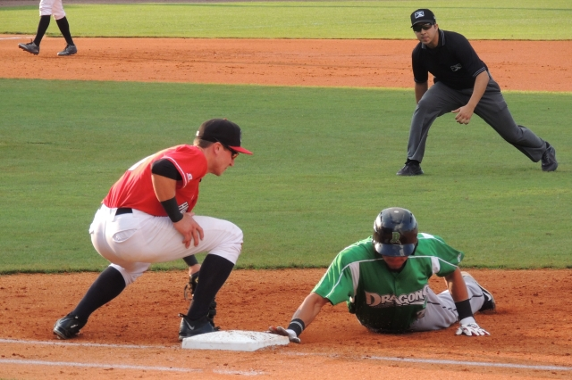 Dragons baserunner Jonathan Reynoso slides back safely to first. Alec Sole is manning the base for the Hot Rods.