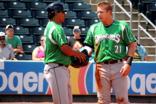 Brian O'Grady (right) hands his helmet to manager Jose Nieves during a Dayton Dragons game last month. (Photo by Craig Wieczorkiewicz/The Midwest League Traveler)