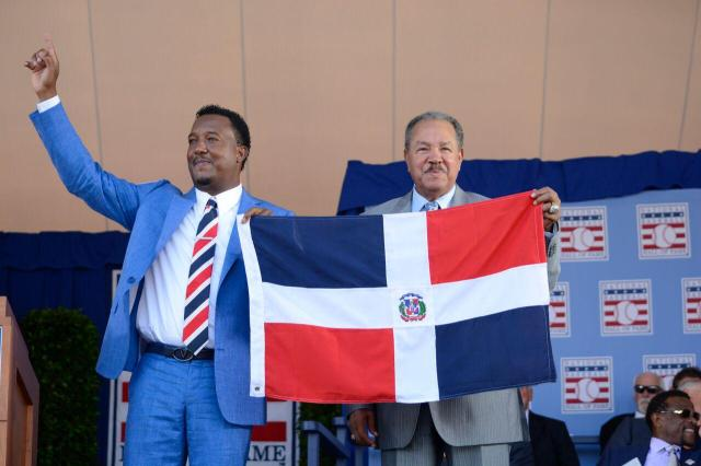 Pedro Martínez (left) and Juan Marichal hold the flag of the Dominican Republic during Sunday's Baseball Hall of Fame induction ceremony. (Photo by Milo Stewart, Jr./National Baseball Hall of Fame)