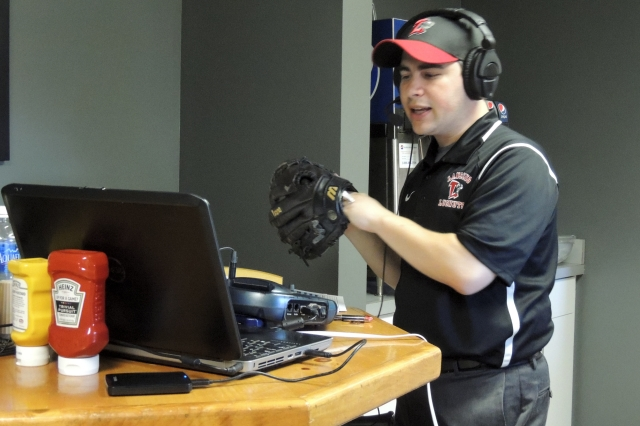 Lansing Lugnuts broadcaster Jesse Goldberg-Strassler uses a ball and glove for sound effects during his annual re-creation broadcast Tuesday.