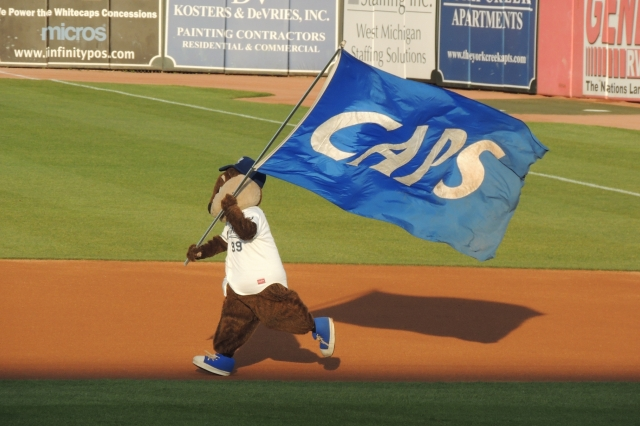 Whitecaps mascot Crash the River Rascal runs with a flag supporting his team before the start of Thursday's game.
