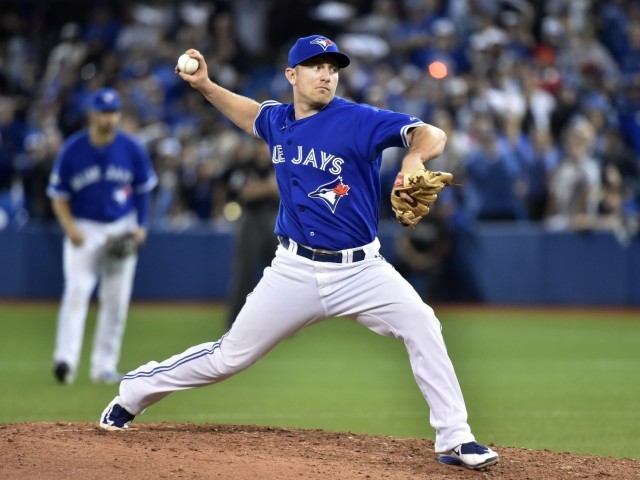 Blue Jays INF Cliff Pennington pitches during the 9th inning of Tuesday's ALCS game in Toronto. (Photo by Nathan Denette/The Canadian Press)