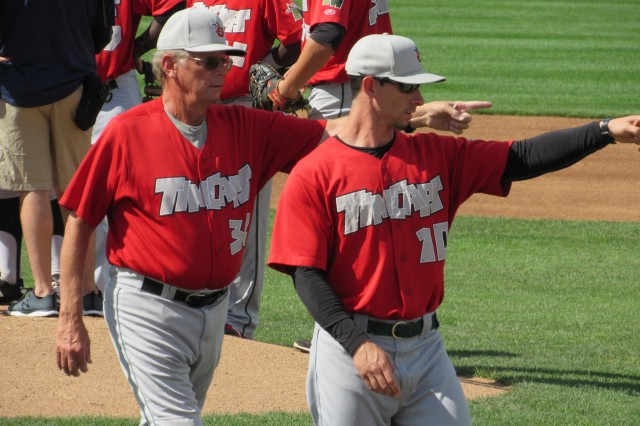 TinCaps pitching coach Burt Hooton (left) and manager Anthony Contreras point toward pitcher Blake Rogers in the bullpen.